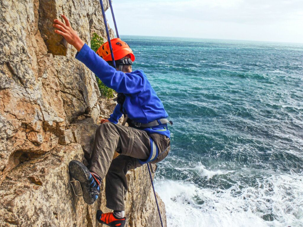 Child climbing on the Dorset coast