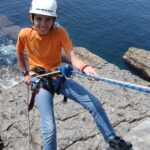 Schoolboy abseiling at Dancing Ledge