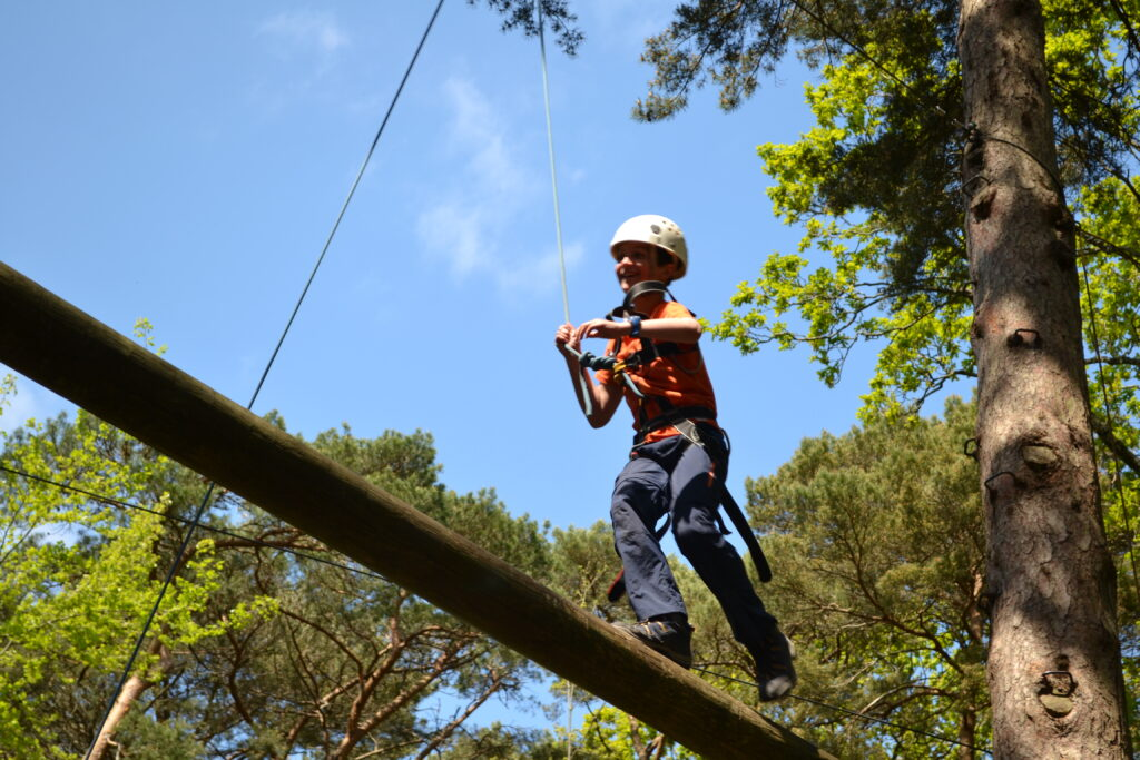Boy running along the high ropes pole