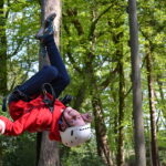 Boy swinging upside down at the ropes course