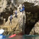 Four people coasteering at Dancing Ledge