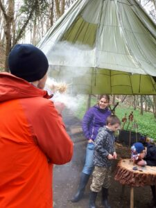Fire blowing with a family group at the Corfe Castle bushcraft site