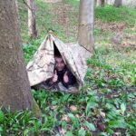 Small boy happy in his new den in the woods