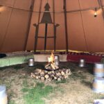 Internal view of a tipi with seating and fire pit