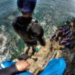 Preparing to jump from a ledge coasteering