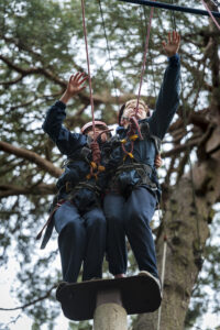 Two girls taking a leap of faith on the tall tower at the ropes course