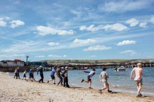 School group skimming stones on Buck Shore Swanage