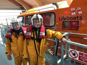 Students experiencing RNLI suits on the lifeboat in Swanage