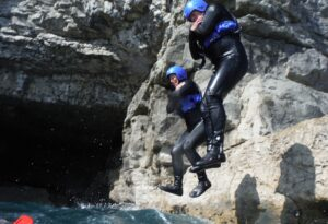 Two adults leaping for the cliffs at Dancing Ledge, coasteering experience
