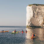 Colourful kayaks on a friend trip at the base of Old Harry Rocks on the Jurassic Coast