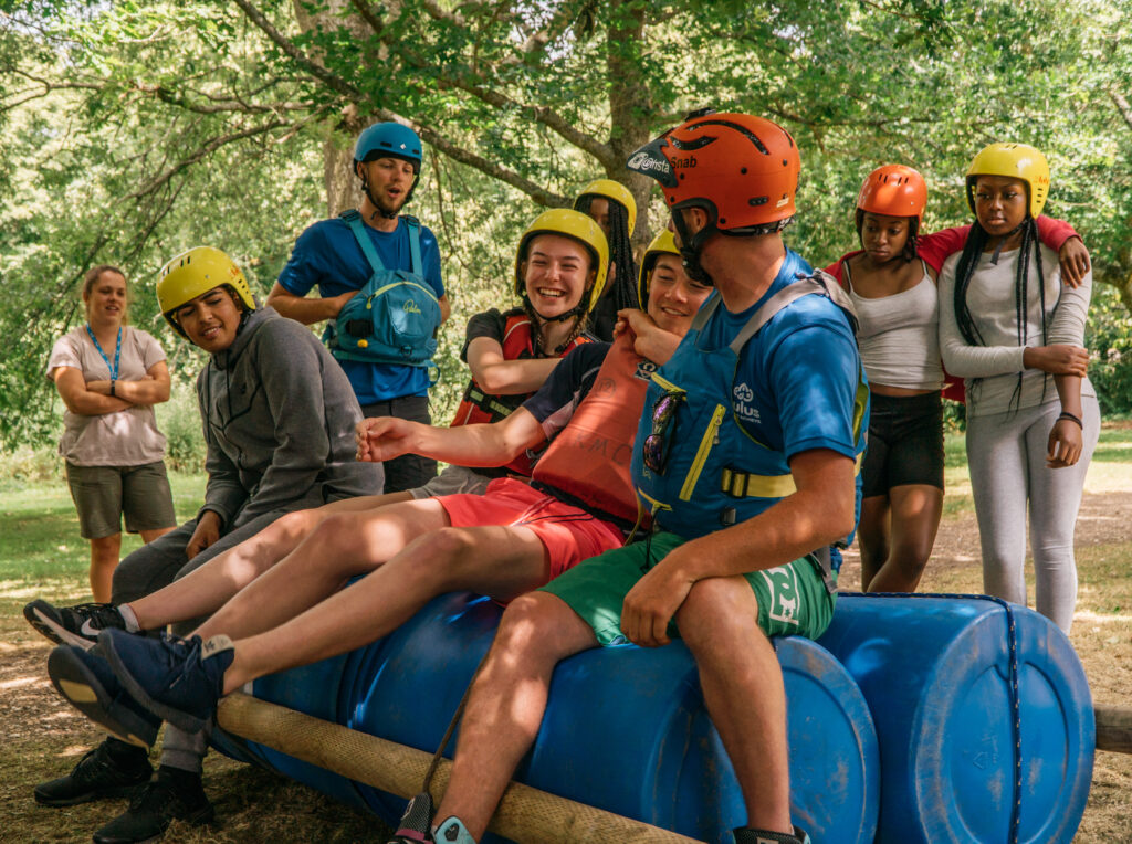 students and staff laughing on raft