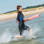 boy running in the sea with Peterson tube