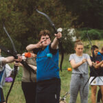 students lining up ready to fire arrows in tag archery